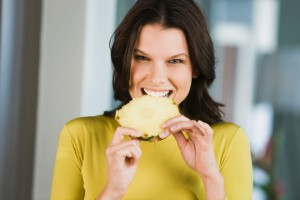 Portrait of a woman eating a slice of pineapple --- Image by © Pascal Broze/Onoky/Corbis