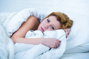 woman in bed sick unable to sleep suffering depression